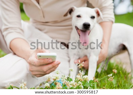 women with dog using smartphone on clover lawn - stock photo