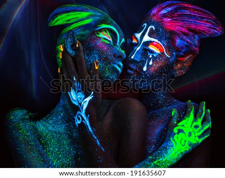 Women with fluorescent body art. Black background. - stock photo
