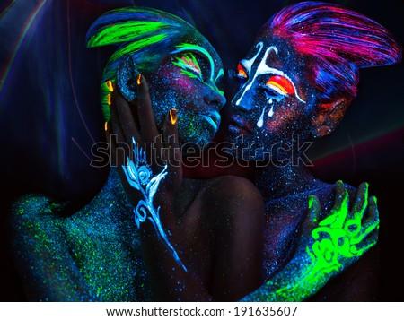 Women with fluorescent body art. Black background. - stock photo
