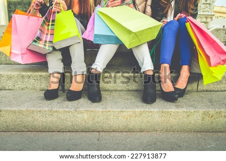 Women with high heels and shopping bags - Three girls sitting on stairs and chatting after buying presents - stock photo