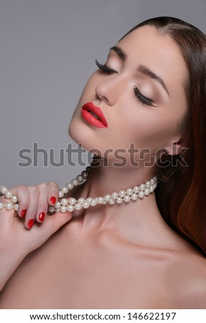 Women with pearl necklace. Portrait of beautiful women touching her pearl necklace and keeping eyes closed while isolated on grey - stock photo