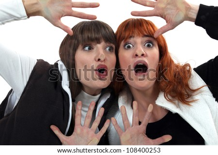 Women with their faces pressed against glass - stock photo