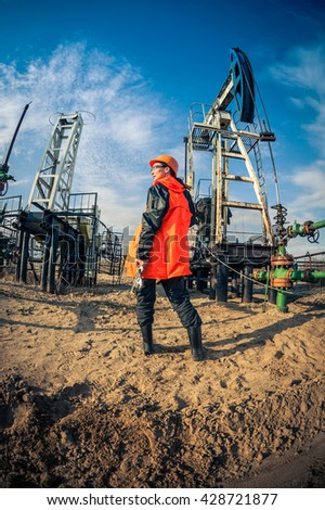 Women worker in the oil field, with wrenches in a hands, orange helmet and work clothes. Industrial site background. - stock photo