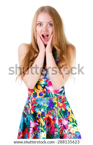 Wondered pretty blonde teenager with wide open eyes and mouth standing and holding hands near her face. Isolated on white background, human emotion, facial expression - stock photo