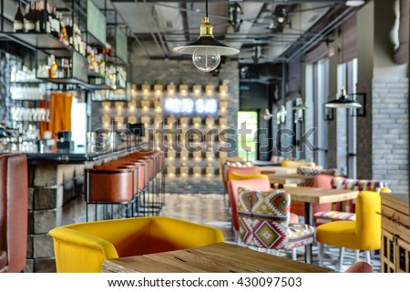 Wonderful bar in a mexican restaurant in a loft style. On the left there is a black bar rack with brown chairs, shelves with dishes and equipment. On the right there are wooden tables with multi - stock photo