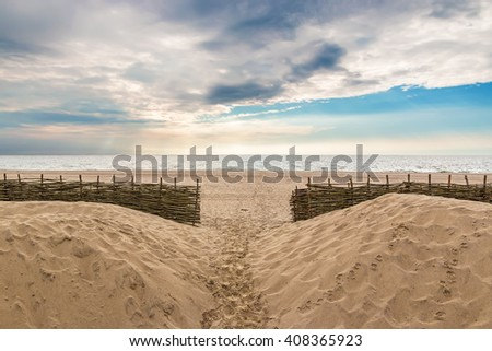 Wonderful cloudy evening on the sandy beach with coastal protection - stock photo