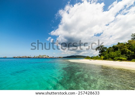 Wonderful colors in the remote Togean Islands, Central Sulawesi, Indonesia. From the white sandy beach to the blue lagoon, with scenic clouds, islets and fishermen village in the background. - stock photo