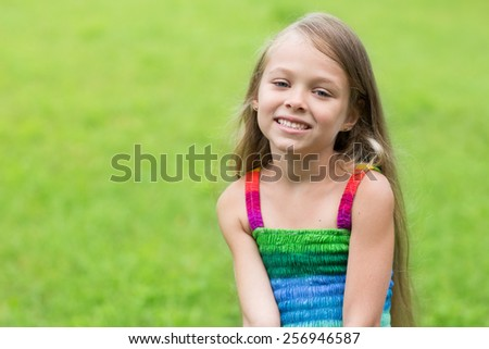 Wonderful happy girl sitting on the lawn. Girl seven years. - stock photo