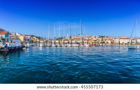 Wonderful romantic old town at Adriatic sea. Boats and yachts in harbor at magical summer. Fishes in the water surface on the foreground. Mali Losinj on the island of Losinj. Croatia. Europe. - stock photo
