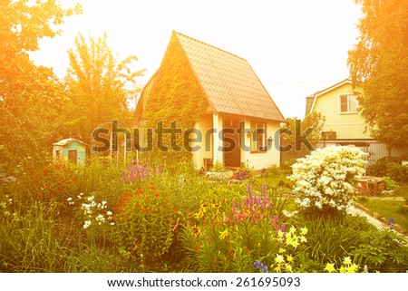 wonderful rustic country house in the lush garden. garden flowers - stock photo