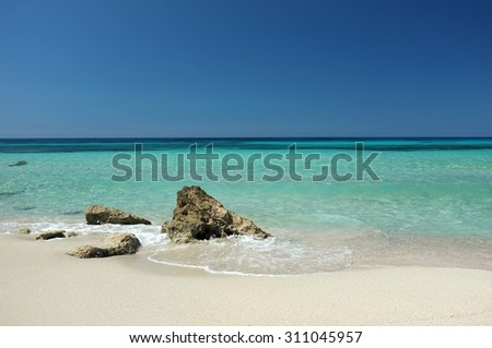 Wonderful sandy beach with some rocks and turquoise clear water - stock photo