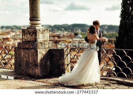 wonderful stylish couple walking on the terrace in sunny weather background cityscape Roma Italy sunshine - stock photo