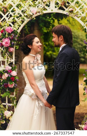 wonderful stylish rich happy bride and groom holding hands look et each other  at a wedding ceremony in green garden near white arch with flowers Rome Italy  - stock photo