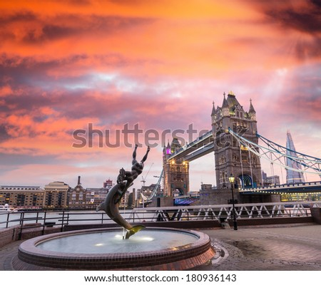 Wonderful sunset sky over Tower Bridge and Dolphin statue - stock photo