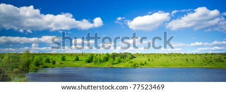 Wonderful view of lake and  green meadow by springtime. - stock photo