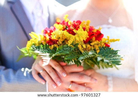 Wonderful wedding bouquet of beautiful colorful flowers which are holding groom and bride together in hands. - stock photo