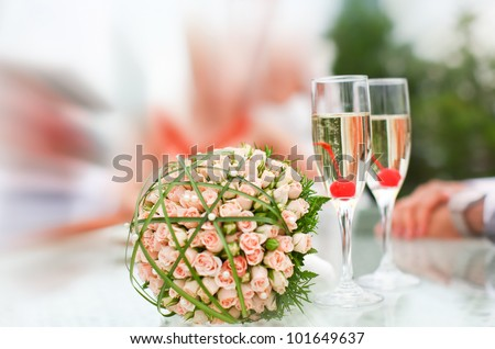 Wonderful wedding luxury bouquet of roses and glasses of champagne with small cherries. - stock photo