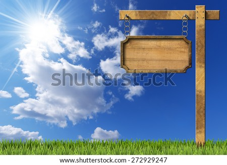 Wood and Metal Sign with Chain and Pole. Empty rectangular wooden sign with metallic brown frame hanging with metal chain on a wooden pole, on blue sky with clouds, sun rays and green grass - stock photo