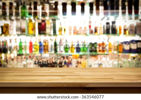Wood bar top on blur colorful alcohol drink bottle background - stock photo