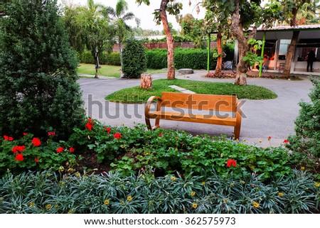 Wood Bench in a flower garden. - stock photo