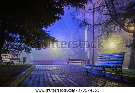 wood benches in the night park in the soft colorful light - stock photo