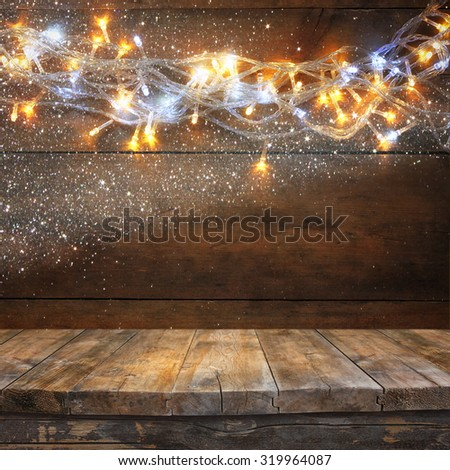 wood board table in front of Christmas warm gold garland lights on wooden rustic background. filtered image. selective focus. glitter overlay - stock photo