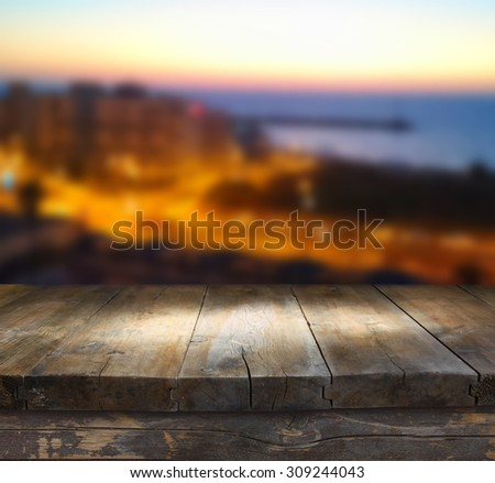 wood board table in front of night sea landscape. Ready for product display montages - stock photo