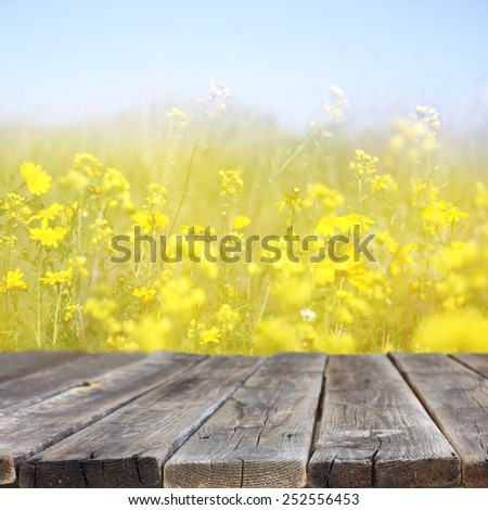wood board table in front of summer landscape with double exposure of flower field bloom  - stock photo