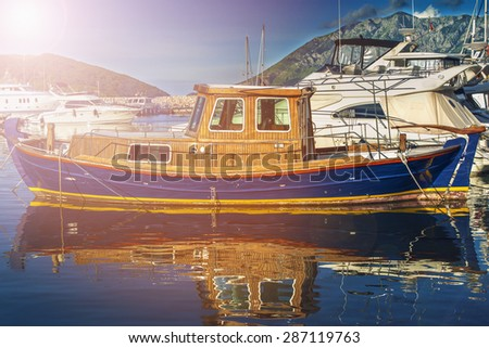 wood boat on the water near the pier behind modern yacht - stock photo