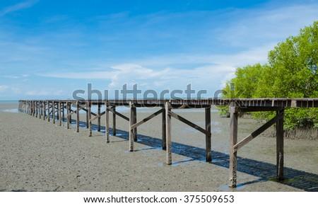 Wood bridge into sea with blue sky background. - stock photo