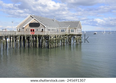 wood building on logs over water at low tide - stock photo