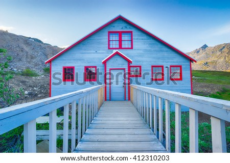 Wood building painted blue with red trim on the Independence Gold Mine from the Alaskan Gold Rush. - stock photo