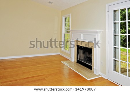 Wood burning fireplace in a room with oak floors flanked by a window and a french door. - stock photo