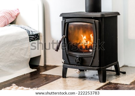 Wood burning stove in bedroom - stock photo