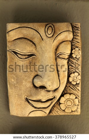 Wood carving in relief of a sculpture of Buddha. - stock photo