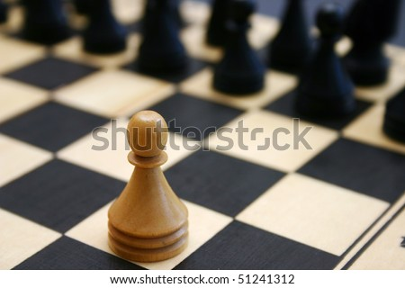 Wood chess game shows white brave pawn challenge stronger enemy. - stock photo