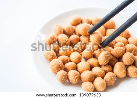 Wood chopstick holding a spicy peanut snack - stock photo