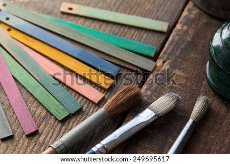 Wood color samples and brushes on an old wooden surface. Focus is on brown brush bristle. - stock photo