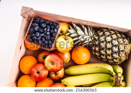 Wood Crate filled with Organic ripe fruit isolated on White - stock photo