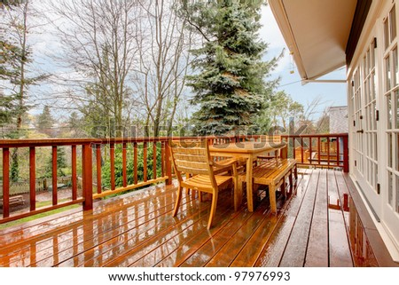 Wood deck during the rain with table and chairs and grey house. - stock photo