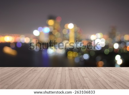 Wood deck with blurred abstract background with bokeh of cityscape of Bangkok's highrise on Chao Phraya River   - stock photo