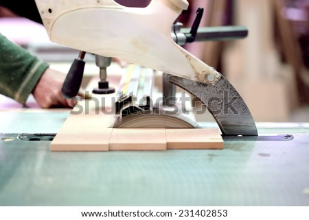 wood factory worker cutting wood boards with sliding compound mitre saw with sharp blade - stock photo