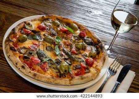 wood fired oven artisan real Italian pizza with grilled roasted vegetable cutlery glass wine vine top view above - stock photo