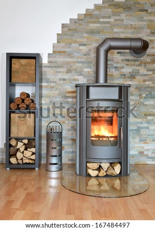 wood fired stove burning with fire-wood. Rack with fire-wood, fire-irons and briquettes in front of brick wall - stock photo