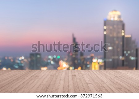Wood floor in light red oak brown color tone w/ blurred abstract background Bangkok cbd city night light rooftop view warm vintage retro style bokeh flare Wooden table+ blur backdrop urban cityscape  - stock photo