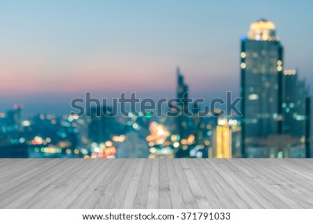 Wood floor in light white grey gray color tone w/ blurred abstract background Bangkok cbd city night light rooftop view cool vintage style bokeh flare: Wooden table w/ blur backdrop of urban cityscape - stock photo