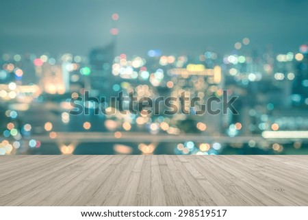 Wood floor in sepia brown color tone with blurred abstract background of Bangkok cbd night light downtown city view w/ bokeh with light flare : Wooden table with blur background of holiday cityscape   - stock photo