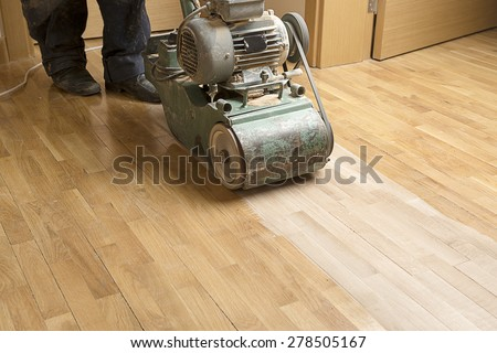 Wood floor polishing maintenance work by grinding machine. - stock photo