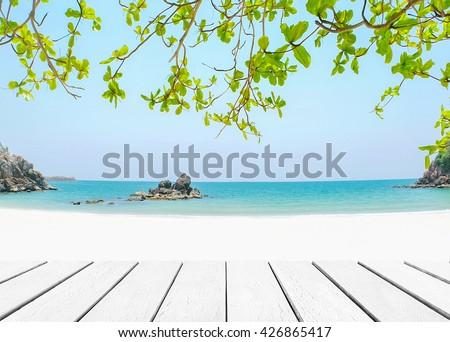 Wood floor with white blue surfing wave background. Blue water and sky bright. Nature wallpaper blur of sea daytime with green laves in the foreground. Focus to wooden timber pattern texture stage. - stock photo