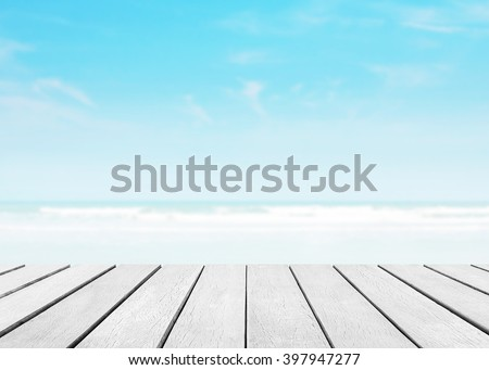 Wood floor with white blue surfing wave background. Blue water on ocean beach and sky bright. Nature wallpaper blur of sea daytime. Focus to wooden in the foreground. Timber pattern texture stage. - stock photo